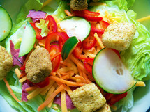 A healthy salad made out of green lettuce, cucumbers, Orange Carrots, Cheddar Cheese and Croutons  for a healthy, delicious salad filled with vitamins to feed the body. If we all treated food as medicine, we would not be so sick or riddled with diabetes, cancer, weight problems, high blood pressure and other ailments brought on by malnutrition and eating the wrong types of food.