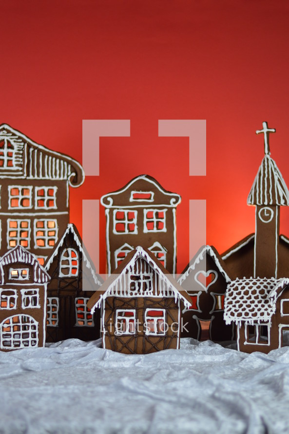 home made gingerbread village in front of red background on white snowlike velvet as advent decoration