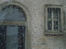 Rain drops on a window overlooking church windows.