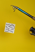 temptation – a piece of paper with words for baits written on at the fishhook of an  angling rod