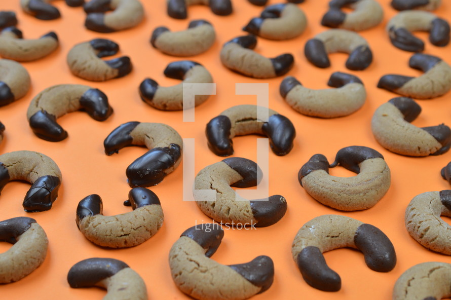 home made nougat crescents cookies with chocolate at the edges on orange background