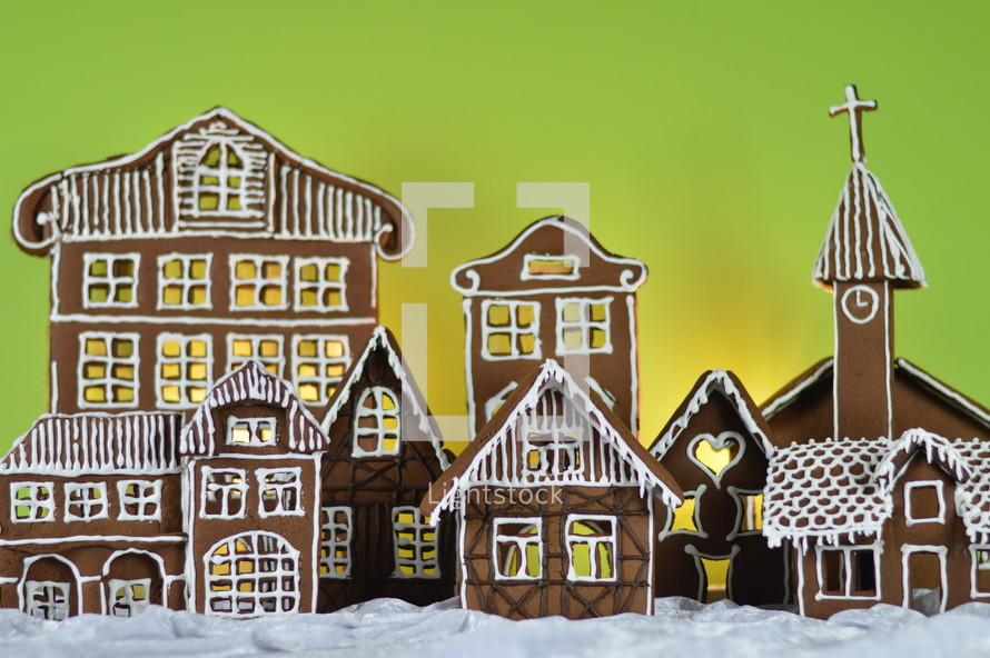 home made gingerbread village in front of yellow and green background on white snowlike velvet as advent decoration