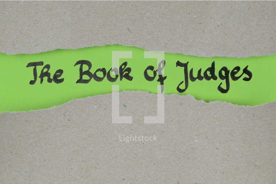 the book of judges - torn open kraft paper over green paper with the name of the book of Judges
