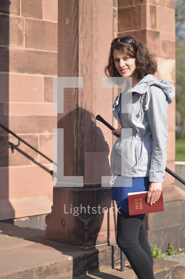 a woman standing on church steps holding a Bible