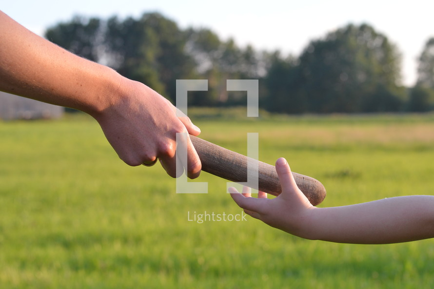 woman giving the relay baton to the next generation into a child's hand