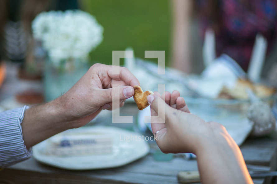 couple holding a heart cracker