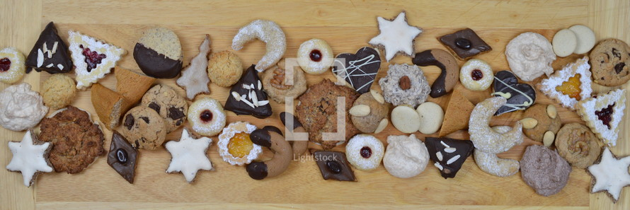 ribbon out of different kinds of Christmas cookies on a breadboard