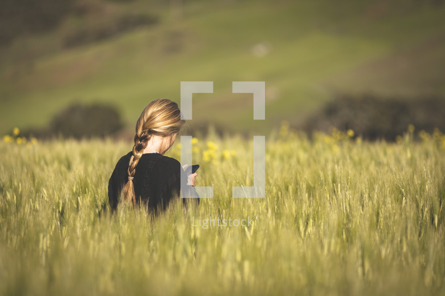 a woman standing in a field of tall grasses holding a cellphone