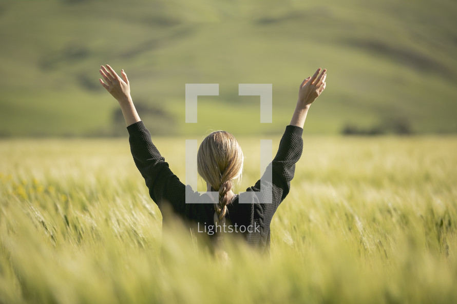 a woman with raised hands standing in a field of wheat