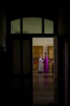 priest and bishop through a door