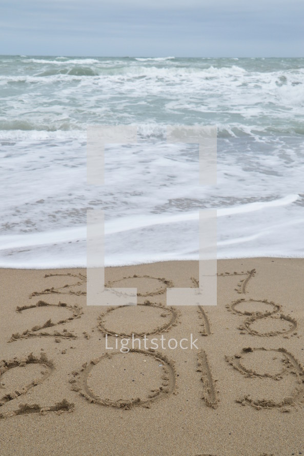 tide washing onto a beach over the years 2017 to 2019 in the sand