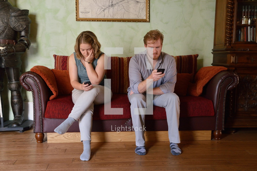 A couple sitting on a sofa looking at their cell phones and ignoring each other.