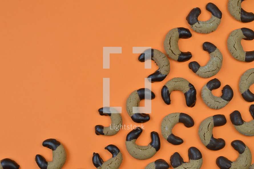 border out of home made nougat crescents cookies with chocolate at the edges and copy space above on orange background