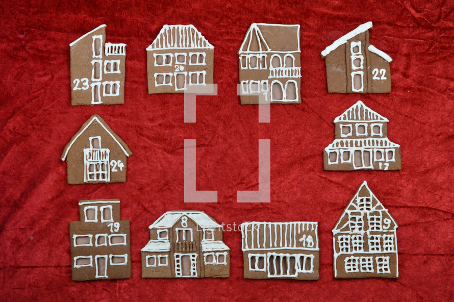 frame out of different self baked gingerbread houses on red with copy space in the middle as part of a advent calendar