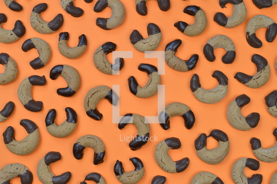 pattern out of home made nougat crescents cookies with chocolate at the edges on orange background