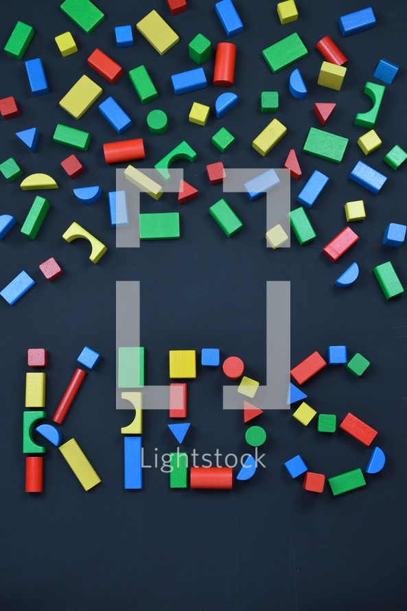 the word KIDS out of colorful wooden toy blocks on black background