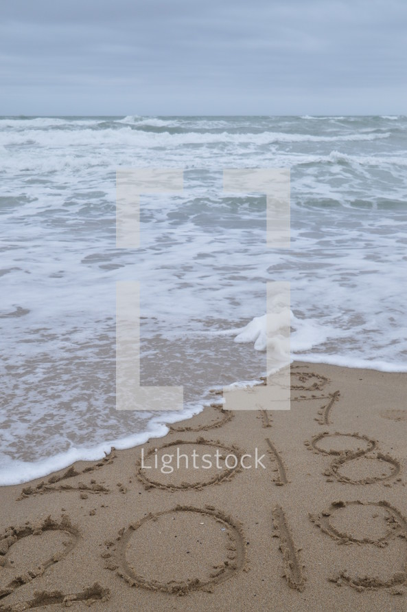 tide washing onto a beach over the years 2016 to 2019 in the sand