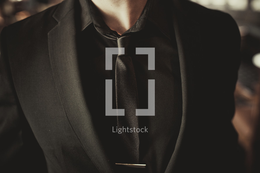 man's torso in a solid black suit