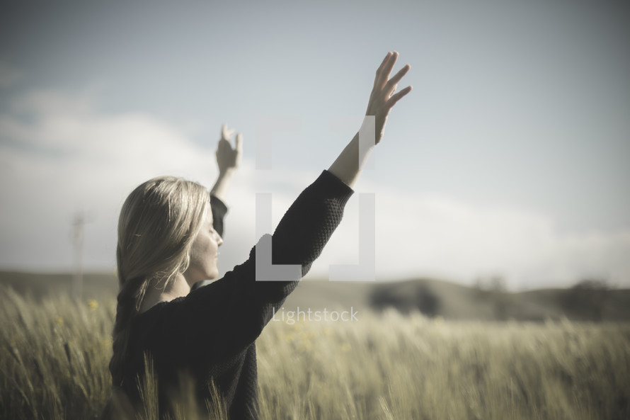 a woman standing in a field of wheat with raised arms