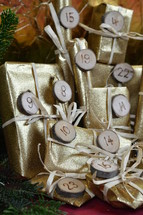 advent calendar with twenty four golden presents on red wood with the numbers burned into round wood pieces