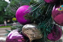 Purple and gold ball ornments hanging from pine Christmas tree.