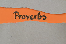 torn open kraft paper over orange paper with the name of the book Proverbs