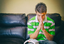 teen boy sitting on a couch praying