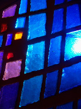 Sun pours through a blue, purple and red stained glass window adding light and color to a prayer chapel during morning worship time.
