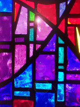The sunlight peaks through a brilliantly colored stained glass window filled with purple, violet, red, lavender and shades of navy to royal blue colors in a church prayer room sanctuary.