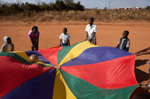 children playing with a ball and parachute in Malawi, Africa.