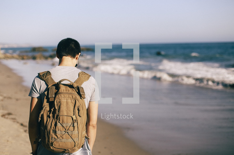 man with a backpack walking on a beach