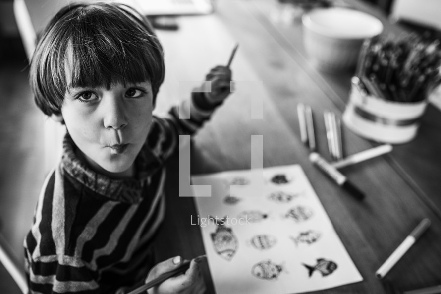 boy coloring on a coloring page at home