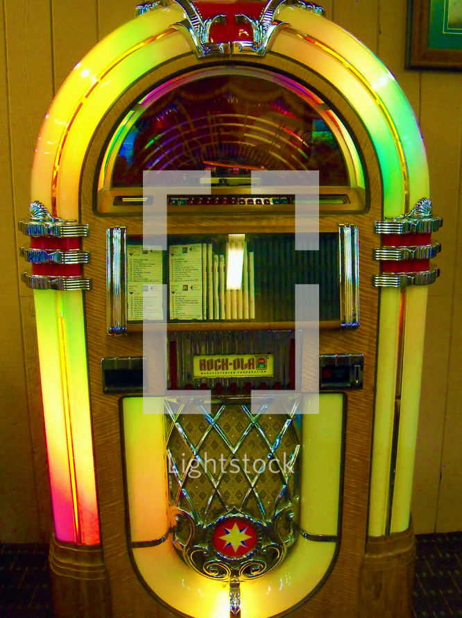 A colorful Music Jukebox from the vintage 1950s to play CD's or Music Tracks at the push of a button. There are some things that are icons from yesterday and yesteryear that should never be forgotten. The Jukebox will definitely be one of those icons that will never be forgotten and can still be found in some local restaurants today to capture that special time in history when a young man or woman could put a quarter in a Jukebox to select a favorite song to listen or dance to together.