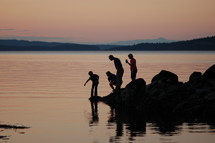 family looking at and pointing at lake water at dusk