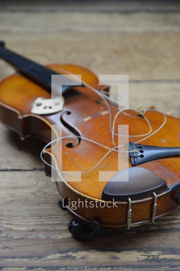 old broken violin on rural wooden floor