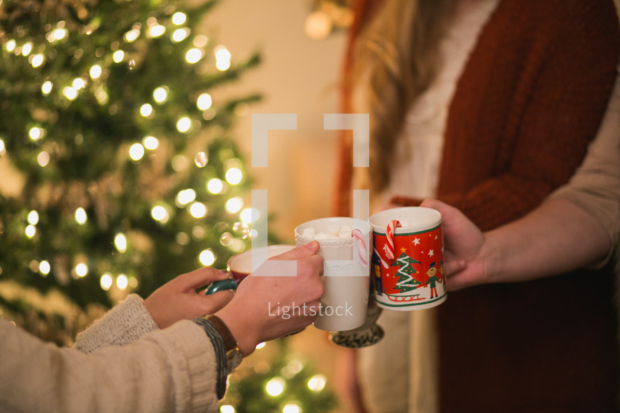 Women put their Christmas cups together in a toast.