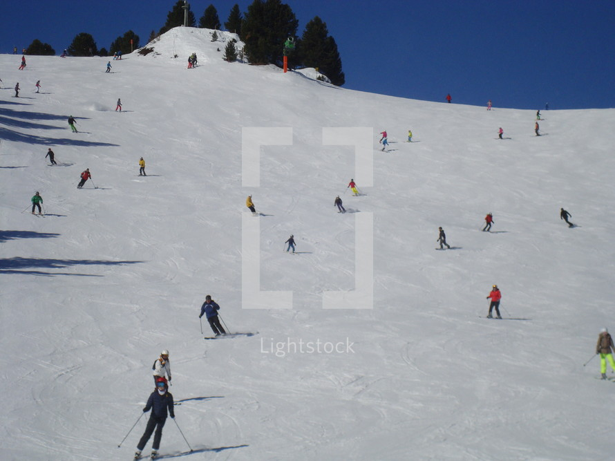 a lot of skiing and boarding people at a ski slope.