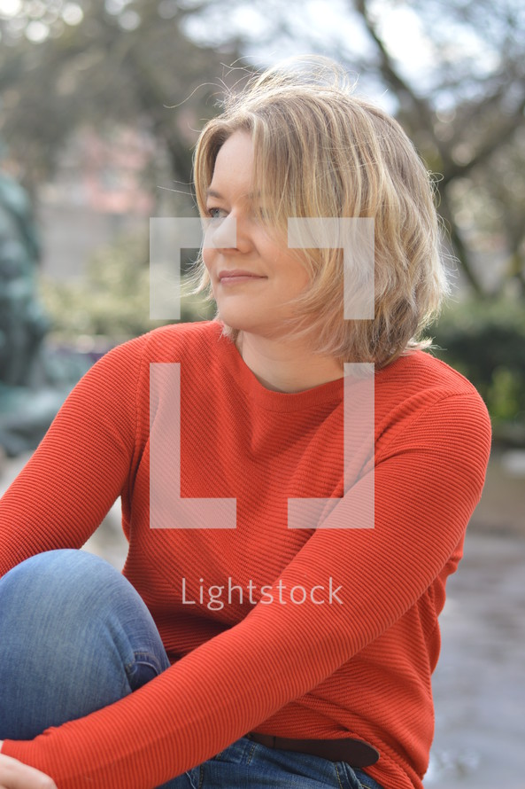 young pretty blond woman with orange pullover sitting outdoors in a park smiling and thinking