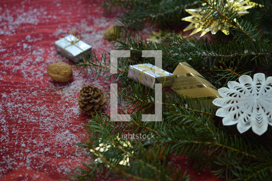 pine, ornaments, snow, and Christmas decorations on a red background
