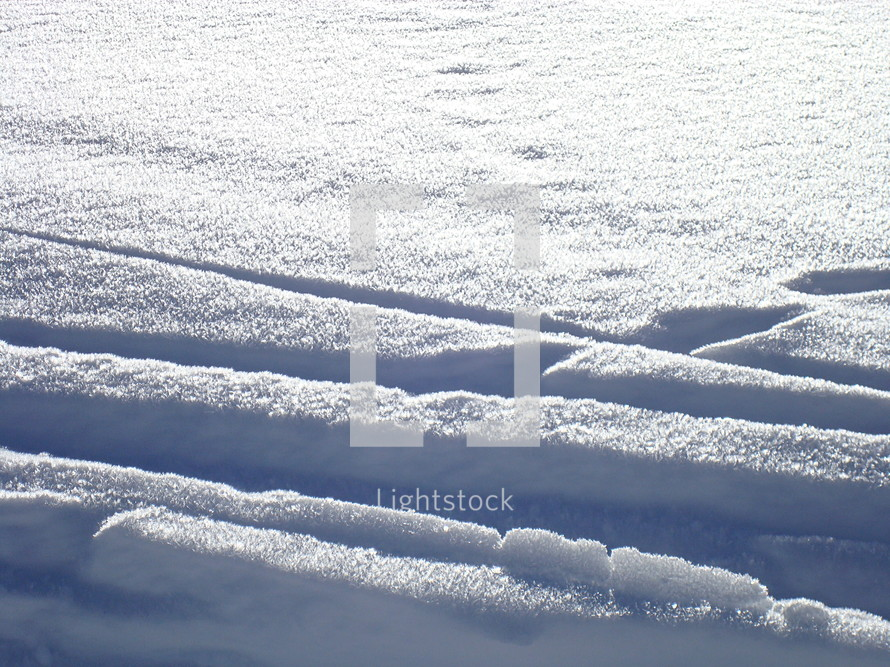 tracks in the snow at a bright day with sunshine.