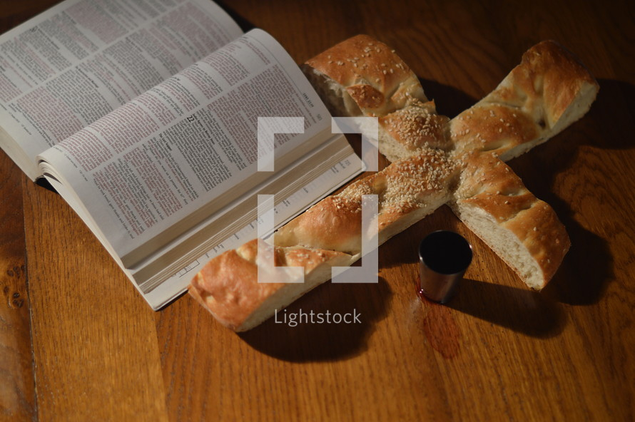 open Bible, bread in the shape of a cross, and cup of communion wine