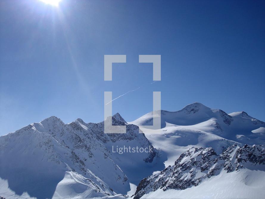 Wintry mountain scene with sun,.