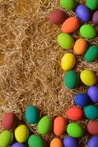 border of colorful Easter eggs on straw