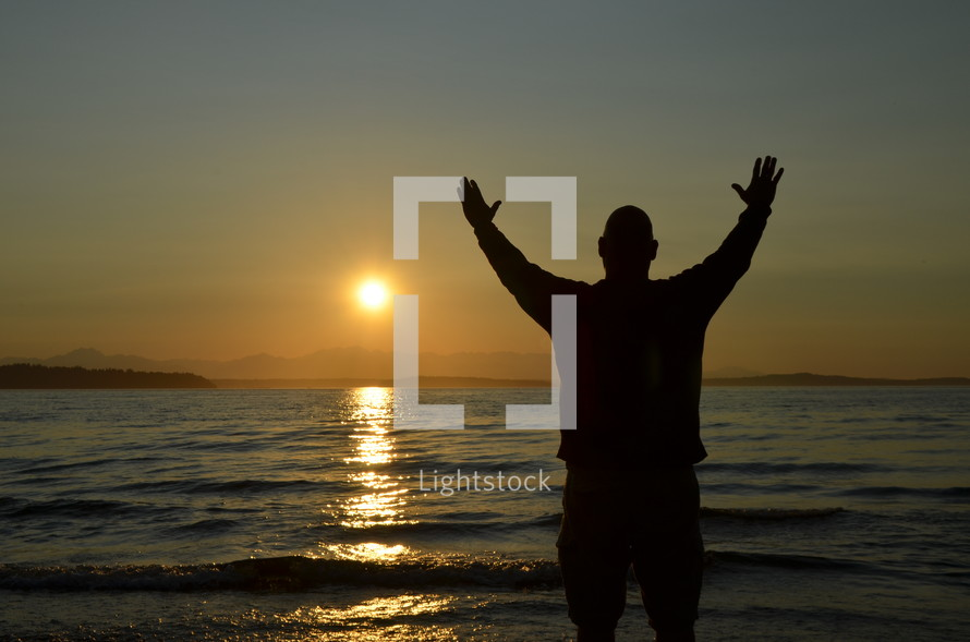 silhouette of a man with hands raised in worship on a beach
