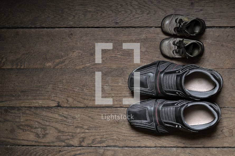 father and son shoes next to each other on a wood floor