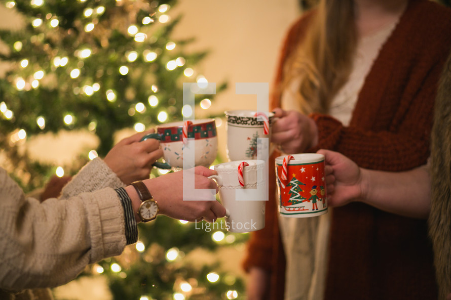 Four women put their Christmas cups together in a toast.