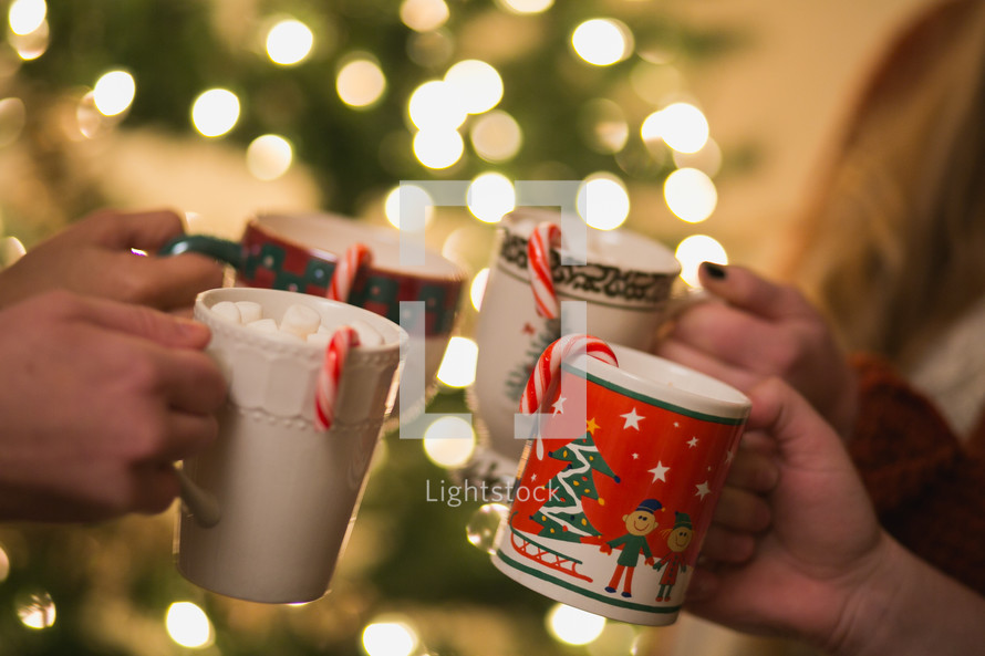 Christmas cups with hot cocoa and candy canes are  put together to make a toast.