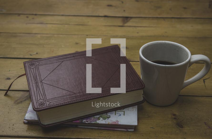 Bible, journal, and coffee mug on a table