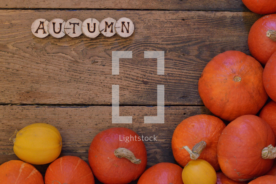 Pumpkins on wooden planks with pieces of wood spelling the word AUTUMN.