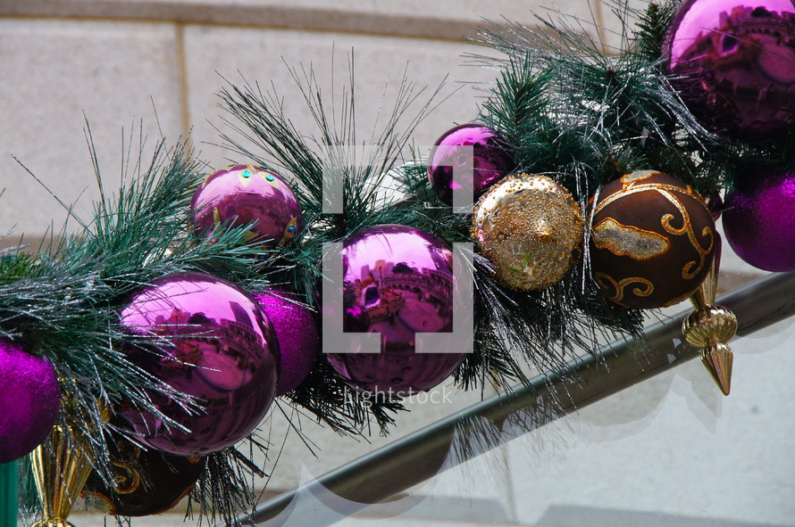 Purple and gold ball Christmas ornaments with pine needle branch along stair rail.